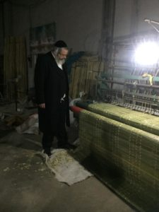 Rabbi checking the bamboo mats